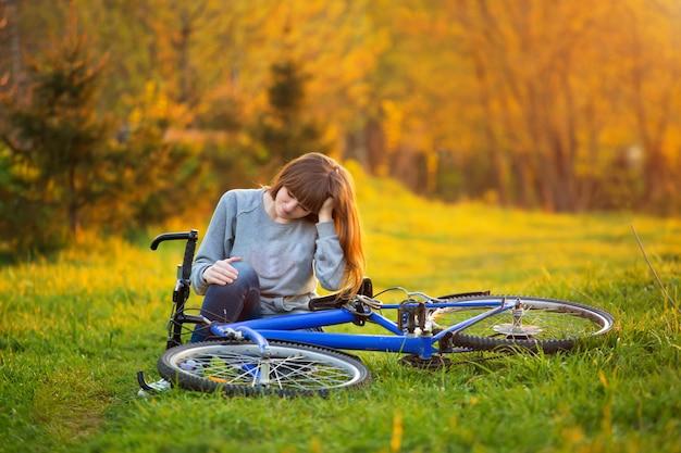 Mulher com dor no joelho depois de andar de bicicleta no parque ao pôr do sol