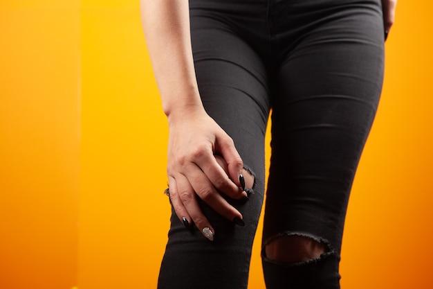 Mulher com dor no joelho em fundo laranja