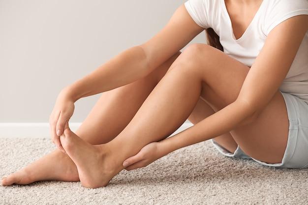 Mulher com dor no pé enquanto está sentada no tapete