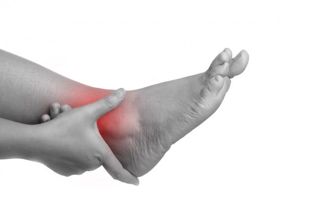 Mulher com dor no tornozelo usando a mão segurando a perna e massageando ela dolorosa
