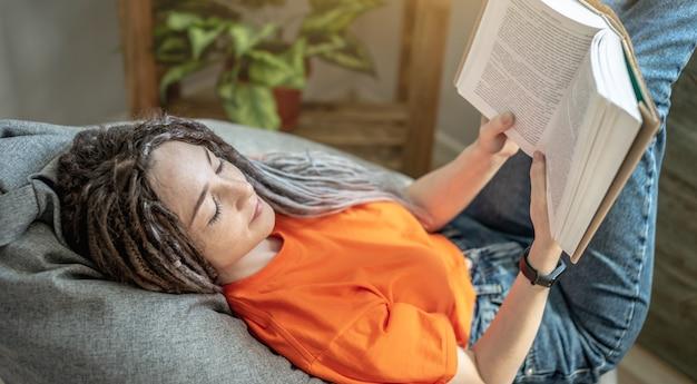 Mulher com dreadlocks e roupas brilhantes está sentada confortavelmente em uma poltrona e lendo um livro
