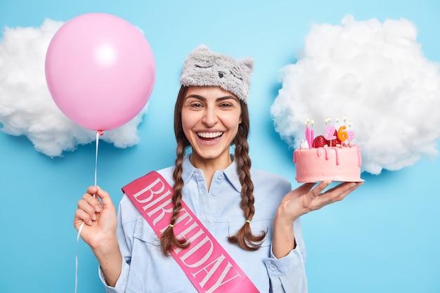 Mulher com duas tranças gosta de festa de aniversário segura bolo de morango balão de hélio inflado se diverte expressa emoções positivas comemora aniversário em casa
