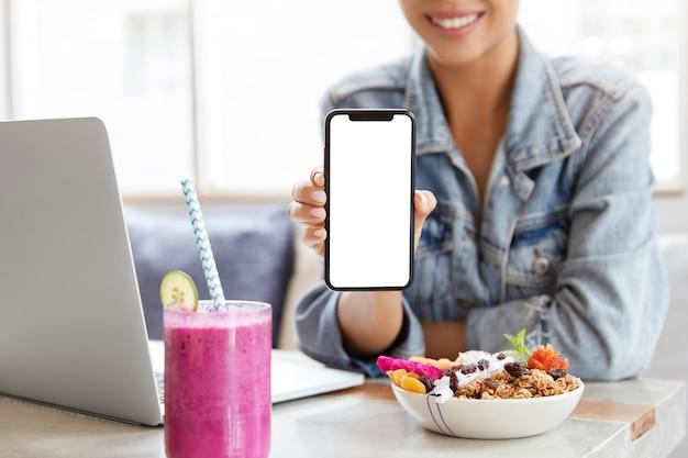 Mulher com elegante jaqueta jeans em um café com a tela do smartphone em branco