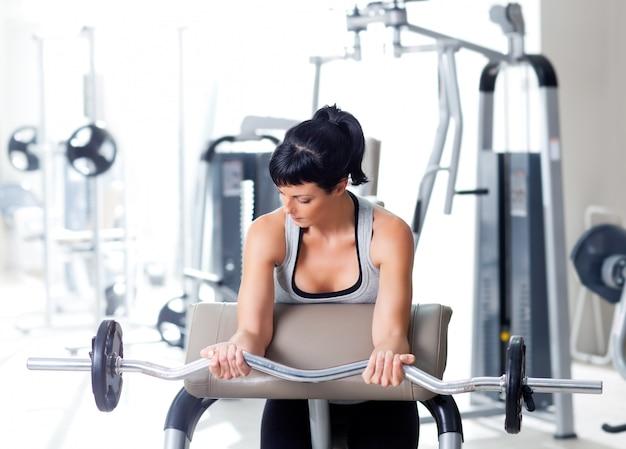 Mulher com equipamento de treinamento de peso no ginásio de esporte
