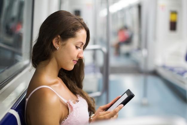 Mulher com ereader no trem de metrô