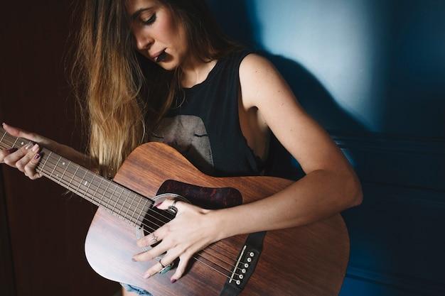 Mulher com escolha tocando violão