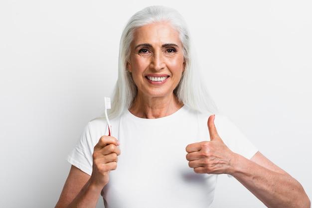 Mulher com escova de dentes com o polegar para cima