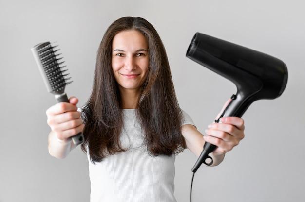 Mulher com escova e secador de cabelo