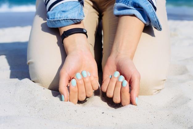 Mulher com esmalte azul nas mãos sentado na areia da praia
