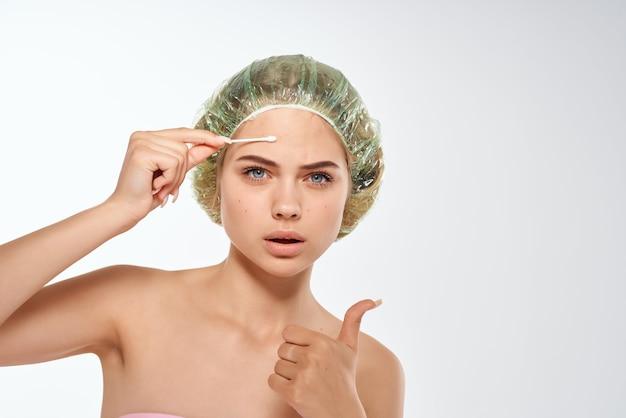 Mulher com espinhas nos ombros nus na testa limpando o rosto