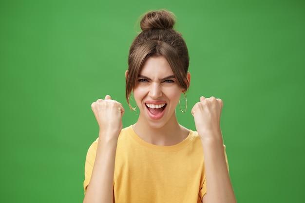 Mulher com espírito de vencedor levantando os punhos cerrados, sorrindo animada e encorajando o apoio sendo rea ...