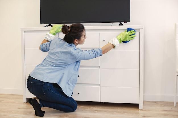 Mulher com esponja e luvas de borracha limpando a casa