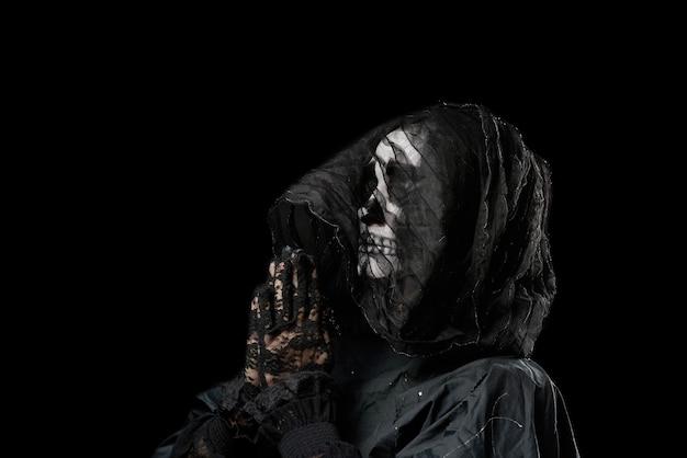 Mulher com esqueleto maquiagem em uma capa preta