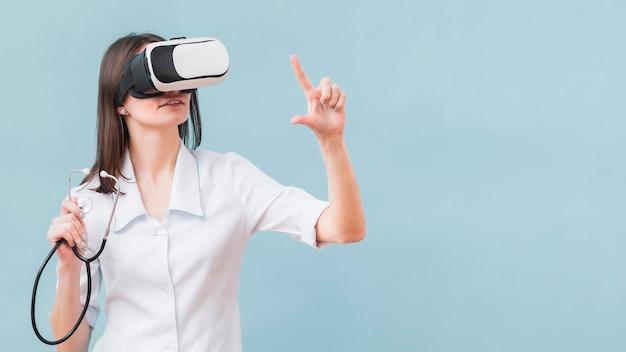 Mulher com estetoscópio usando fone de ouvido de realidade virtual