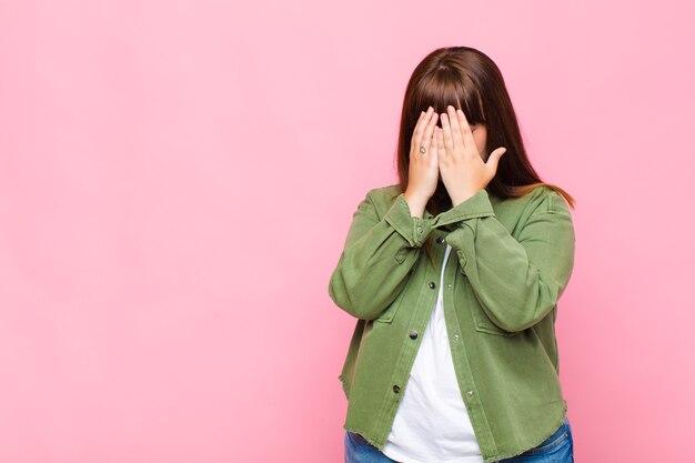Mulher com excesso de peso cobrindo os olhos com as mãos com um olhar triste e frustrado de desespero, chorando, vista lateral