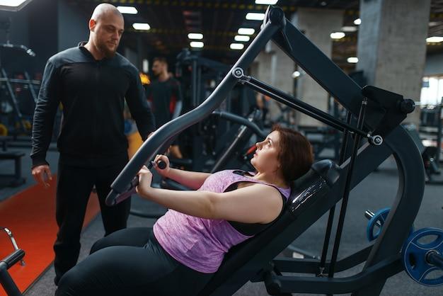 Mulher com excesso de peso com treinador fazendo exercícios na academia, treinamento físico com instrutor