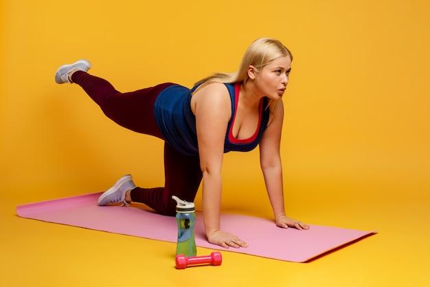 Mulher com excesso de peso faz ginástica em casa. expressão determinada.
