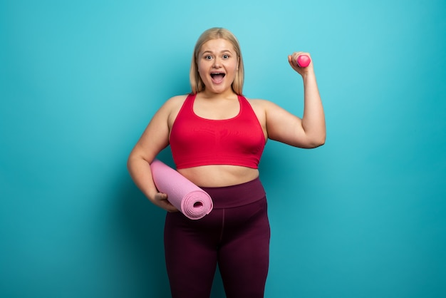 Mulher com excesso de peso faz ginástica em casa. expressão satisfeita.