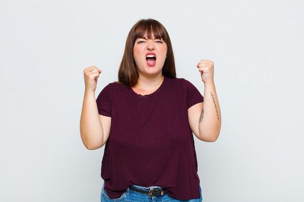 Mulher com excesso de peso gritando agressivamente com uma expressão de raiva ou com os punhos cerrados celebrando o sucesso