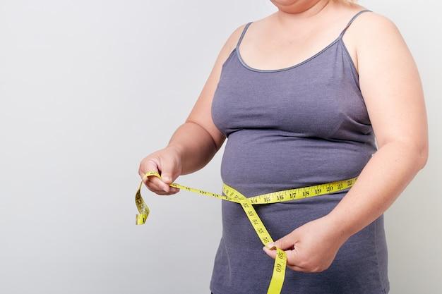 Mulher com excesso de peso, medindo sua barriga gorda