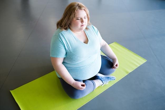 Mulher com excesso de peso meditando