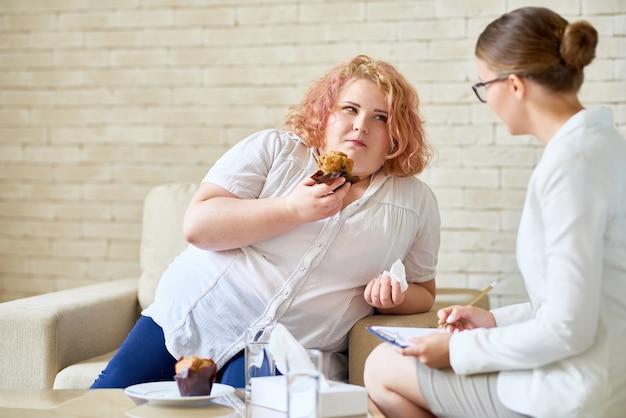 Mulher com excesso de peso que sofre de transtorno alimentar