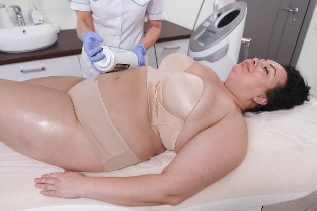 Mulher com excesso de peso relaxando em um salão de beleza, recebendo massagem adelgaçante de endosferas