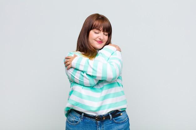 Mulher com excesso de peso se sentindo apaixonada, sorrindo, acariciando e se abraçando, permanecendo solteira, sendo egoísta e egocêntrica