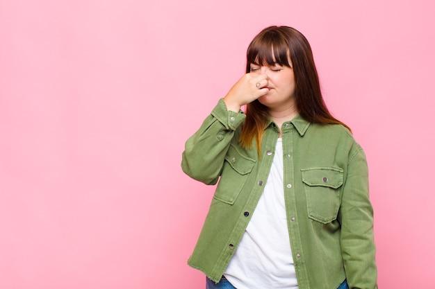 Mulher com excesso de peso se sentindo enojada, segurando o nariz para evitar cheirar um fedor desagradável e desagradável