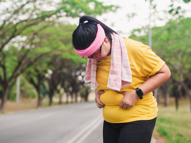 Mulher com excesso de peso, segurando a barriga. conceito de perda de peso