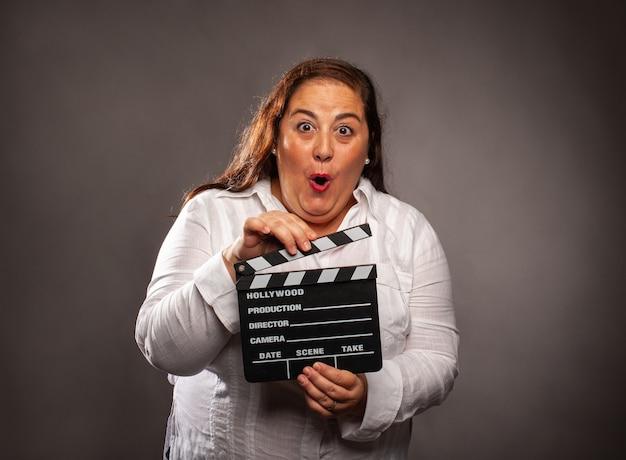 Mulher com excesso de peso segurando uma claquete de cinema em um fundo cinza