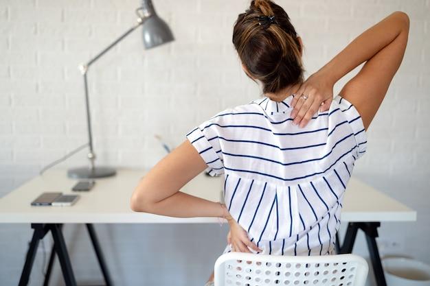 Mulher com excesso de trabalho e dor nas costas no escritório, sentada na cadeira com má postura