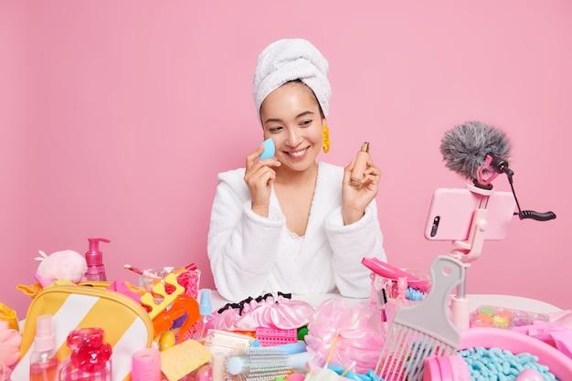 Mulher com expressão feliz aplica base no rosto usa mídia social para vídeo de registros de marketing para poses de blog de beleza na câmera do smartphone isolada na parede rosa. tradução online