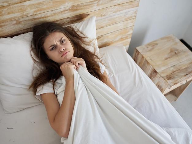 Mulher com expressão triste na cama debaixo do cobertor pela manhã