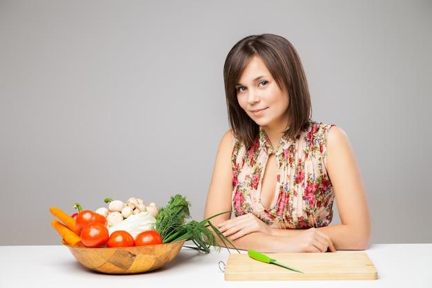 Mulher com faca vai preparar o café da manhã com diferentes vegetais na mesa da cozinha