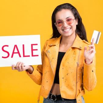 Mulher com faixa de venda de jaqueta amarela e cartão de crédito