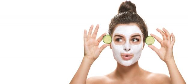 Mulher com fatias de máscara e pepino faciais nas mãos dela