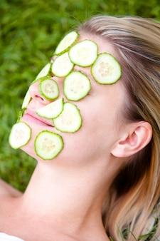 Mulher com fatias de pepino sobre o rosto