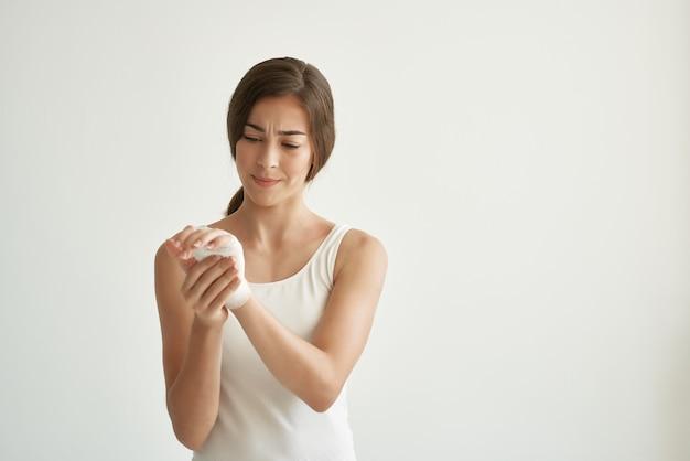 Mulher com ferimento no braço enfaixado problemas de saúde luz de fundo