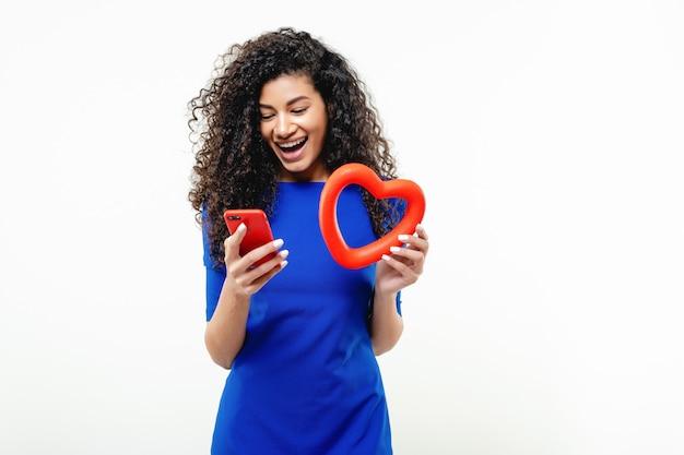 Mulher com figura de coração vermelho e telefone sorrindo isolado