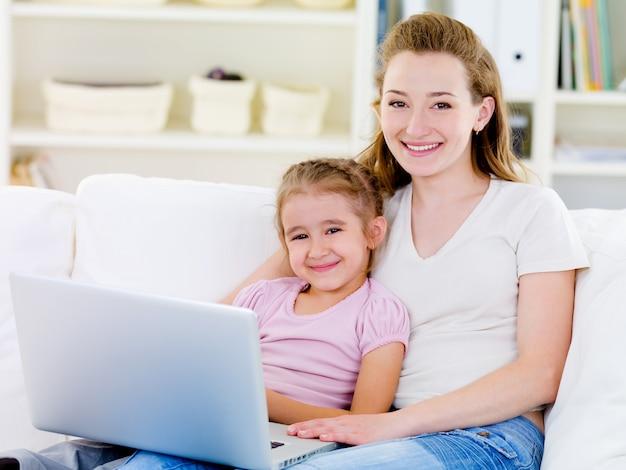 Mulher com filha com laptop