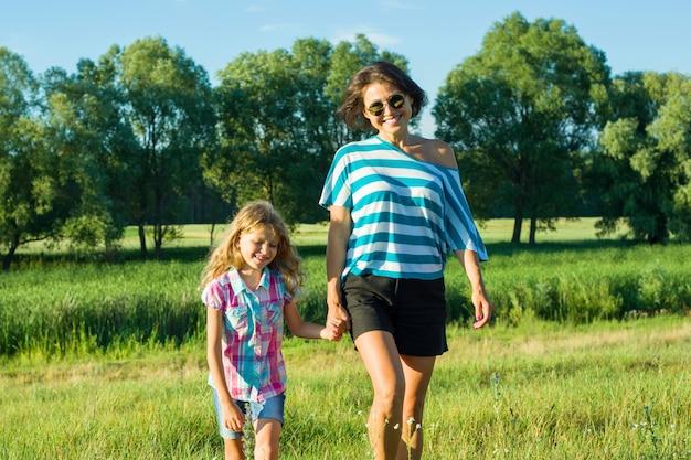 Mulher com filha criança andando na natureza, de mãos dadas.