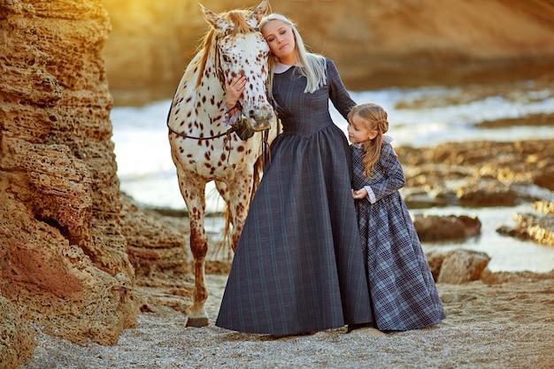 Mulher com filha e cavalo malhado