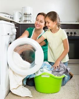 Mulher com filha perto de máquina de lavar