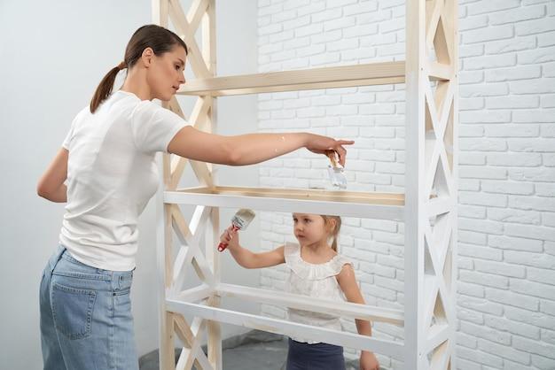Mulher com filha pintando rack de madeira