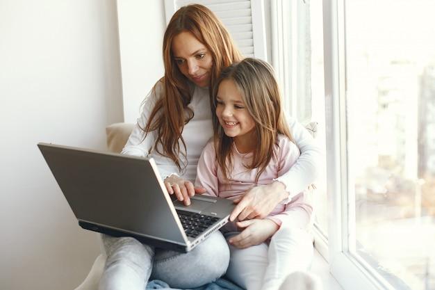 Mulher com filha usando laptop