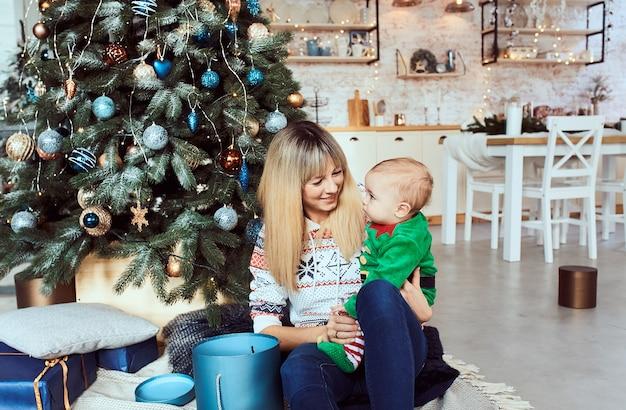 Mulher com filho pequeno sentada na árvore de natal