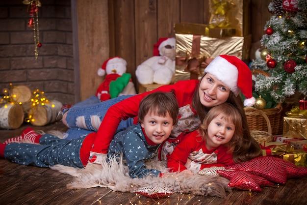 Mulher com filhos deitada ao lado da árvore de natal
