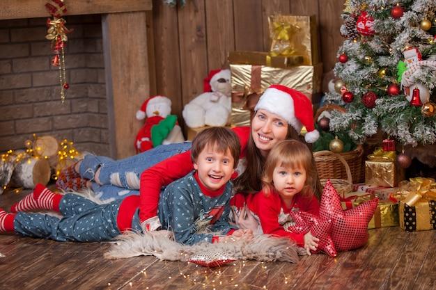 Mulher com filhos, deitada na pele com um chapéu de papai noel ao lado da árvore de natal