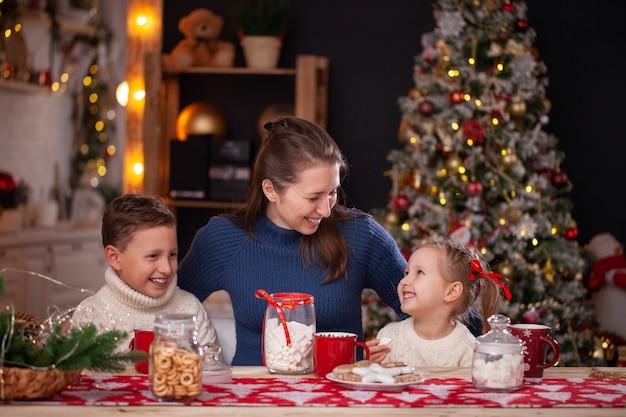Mulher com filhos em uma cozinha decorada de natal